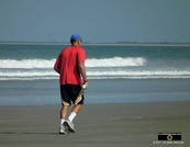 Picture of a man in a red shirt and blue ballcap, jogging on the beach. © 2011, FreePhotoCourse.com, all rights reserved.  Awesome beach pictures & wallpapers. Download free jpg, jpeg photos.