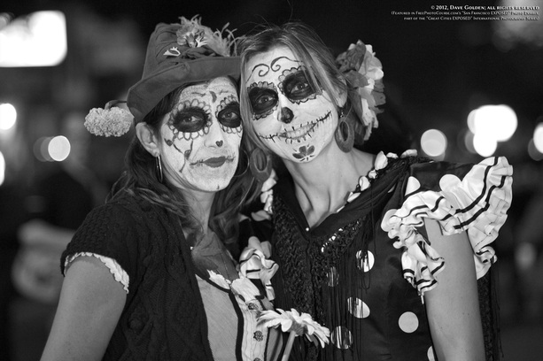 Black & white picture of two women with skeletal face paint and costume, celebrating  Dia De Los Muertos (Day of the Dead) in San Francisco, California.