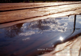 Sky Reflected in Puddle on Deck - Fine Art Photography Tips and Lessons - © 2010, Kevan Donais.  Visit www.FreePhotoCourse.com, all rights reserved