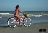 Downloadable picture of a girl wearing a pink bikini, riding her matching pink bicycle on the beach.© 2011, FreePhotoCourse.com, all rights reserved.  Awesome beach pictures & wallpapers. Download free jpg, jpeg photos.