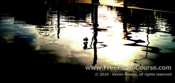 Picture of distorted reflection in curbside puddle.  Visit www.FreePhotoCourse.com for free photography tips, lessons, pictures and more!
