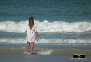 Picture of an attractive woman wearing a man's shirt, standing at the water's edge on a beach. © 2011, FreePhotoCourse.com, all rights reserved.  Awesome beach pictures & wallpapers. Download free jpg, jpeg photos.