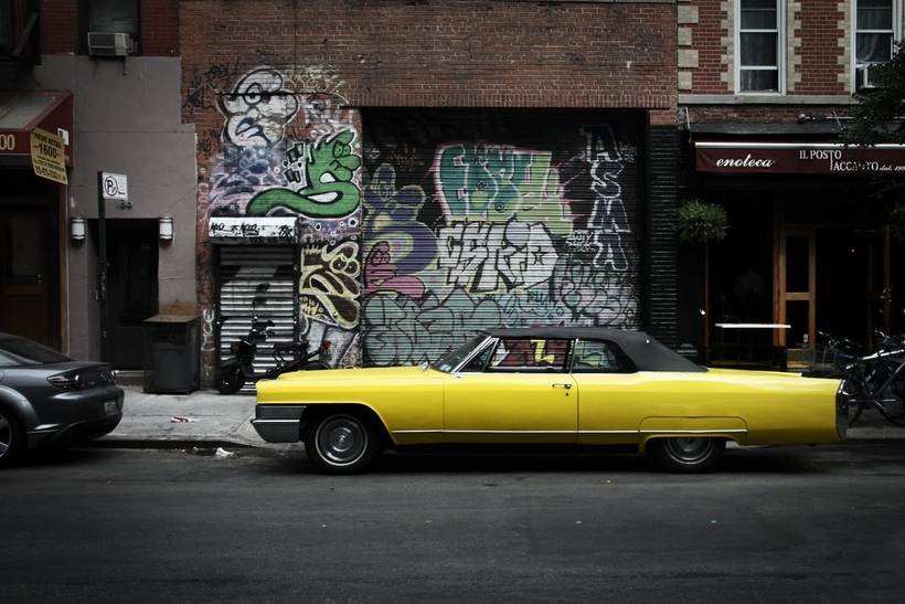 Picture of a yellow rag top muscle car parked in front of a heavily 'decorated' wall and garage door in the East Village, NYC; shot by Stan Baranski; part of the www.FreePhotoCourse.com New York Photo Exhibit 'NYC Exposed'; all rights reserved