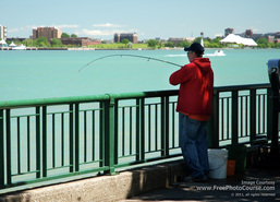 Picture of a man fishing at the railing along a river's edge.  Find more free pictures and wallpapers at www.FreePhotoCourse.com.  © 2011, FreePhotoCourse.com; all rights reserved.