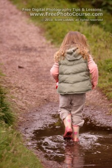 Picture of a child walking through a mud puddle with reflection of feet and legs.  Visit www.FreePhotoCourse.com for free digital photography tips, lessons and more.