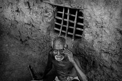 Picture of an old man sitting in a primitive mud hut in India.  His window is a simple lattice of wooden sticks set into the mud.  Illustrates the desperate conditions for many of the country's inhabitants. Part of the Photographer Profiles series at FreePhotoCourse.com. © 2010, Soham Gupta, all rights reserved.