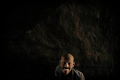 Picture of an Indian man sitting in the darkness of an impoverished existance, a mud wall behind him.  Despite the conditions, he wears a smile and his eyes are bright and happy.Part of the Photographer Profiles series at FreePhotoCourse.com. © 2010, Soham Gupta, all rights reserved.