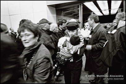 Dramatic picture of a French airline stewardess holding a child refugee in a busy airport. Picture is a link to www.FreePhotoCourse.com's Photographer Profiles series.  Photo Credit: Matthieu Alexandre, (c) 2010, all rights reserved.