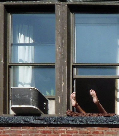 Picture of a man's legs and feet hanging out of a New York City apartment window. Photographed by Bobbie Turner, part of the FreePhotoCourse.com 'NYC Exposed' photography exhibit; all rights reserved.
