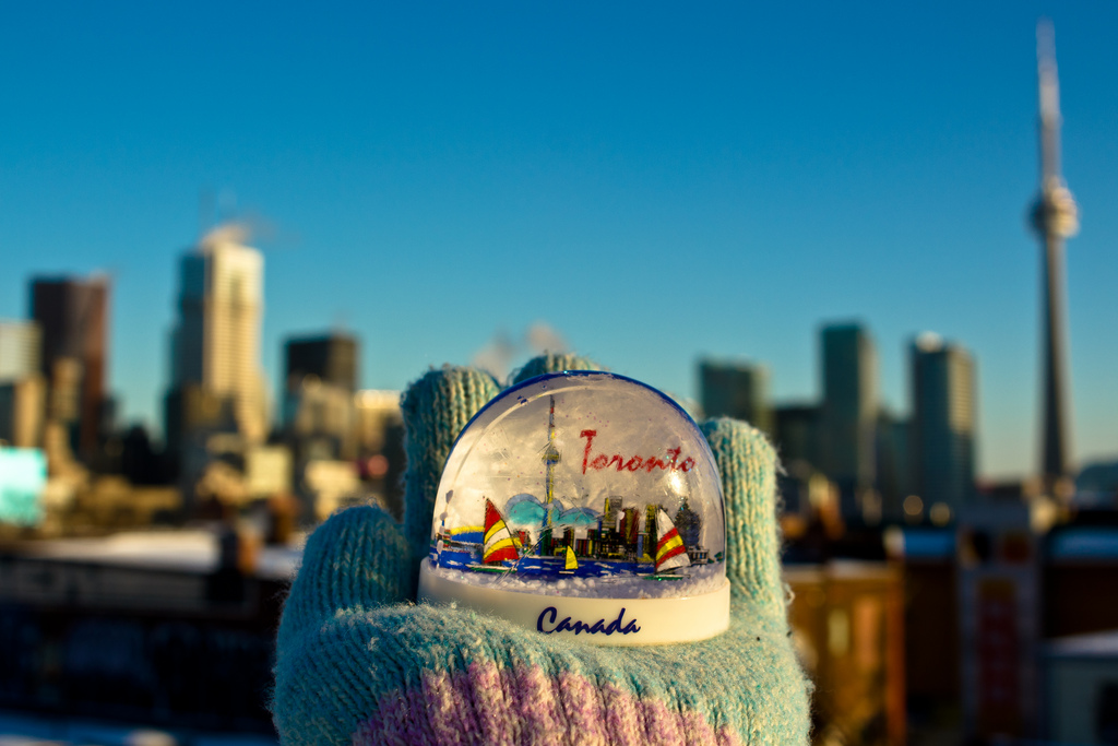 Picture of a mittened hand holding a snow globe in front of the Toronto, Ontario skyline.  Honorable Mention featured in FreePhotoCourse.com