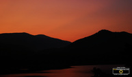 Picture of a stunning sunset over mountains and lake. Download free pictures and wallpapers.  © 2011, FreePhotoCourse.com, all rights reserved.