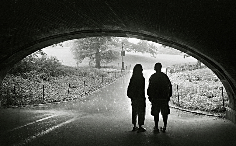 Picture of a young couple, silhouetted, taking shelter from the rain under a Central Park bridge.  Photo Credit: Joe Constantino.  Part of the popular online photography exhibit, NYC Exposed, from http://www.FreePhotoCourse.com.  All rights reserved.