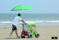 Picture of a man pushing his ice-cream cart on a beach. © 2011, FreePhotoCourse.com, all rights reserved.  Awesome beach pictures & wallpapers. Download free jpg, jpeg photos.