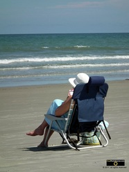 Serene picture of a woman relaxing in a folding chair at the sea shore.© 2011, FreePhotoCourse.com, all rights reserved.  Awesome beach pictures & wallpapers. Download free jpg, jpeg photos.