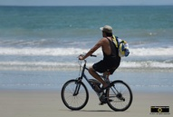 Interesting picture of a man with a backpack, riding his bicycle on the beach.© 2011, FreePhotoCourse.com, all rights reserved.  Awesome beach pictures & wallpapers. Download free jpg, jpeg photos.