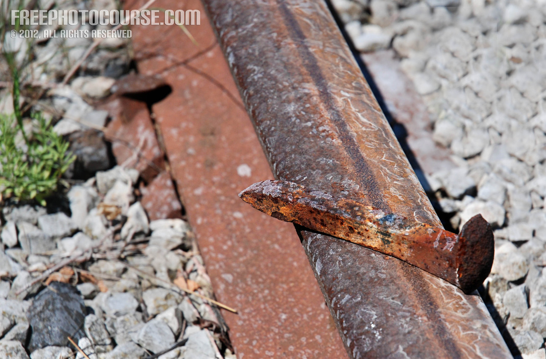 Picture of a rusty old iron spike on an abandoned railway track.  Part of a photo composition tutorial by FreePhotoCourse.com; © 2012, all rights reserved.