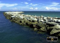 Picture of a rocky jetty at the mouth of an ocean port.  Find more cool pictures and wallpapers at FreePhotoCourse.com. © 2011, all rights reserved.