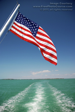 Picture of an American flag hanging off the back of a large boat; wake behind boat is visible in the inviting blue-green water.  Find more great free photos and wallpapers at http://www.FreePhotoCourse.com. © 2011, FreePhotoCourse.com; all rights reserved.