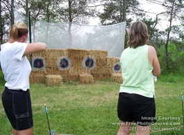 Picture of two women practicing archery.  Bow & Arrow with targets on bales of hay; © 2011, FreePhotoCourse.com, all rights reserved