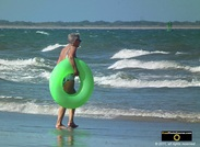 Picture of an elderly woman holding a green swimming tube at the beach. © 2011, FreePhotoCourse.com, all rights reserved.  Awesome beach pictures & wallpapers. Download free jpg, jpeg photos.