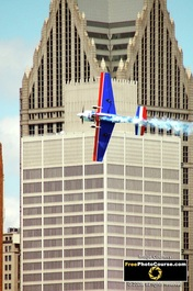 Picture of a stunt plane flying past downtown city skyscrapers.© 2011, FreePhotoCourse.com, all rights reserved.  Free high-res desktop wallpapers and pictures.