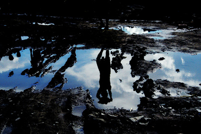 Beautiful artistic photography; picture depicts an abstract reflection of human figures and blue sky in puddles dotted in the soil. Part of the Photographer Profiles series at FreePhotoCourse.com. © 2010, Soham Gupta, all rights reserved.