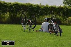 Picture of two cyclists taking a break and resting on a lawn.© 2011, FreePhotoCourse.com, all rights reserved.  Free high-res desktop wallpapers and pictures.