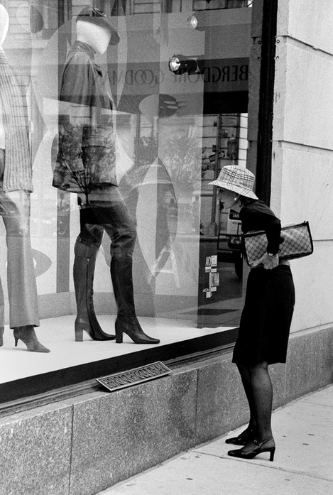 Picture of a well-dressed woman looking into the window display at Bergdorg-Goodman in New York City; photo credit: Joseph Consantino; part of the 'NYC Exposed' photography exhibit at FreePhotoCourse.com; all rights reserved