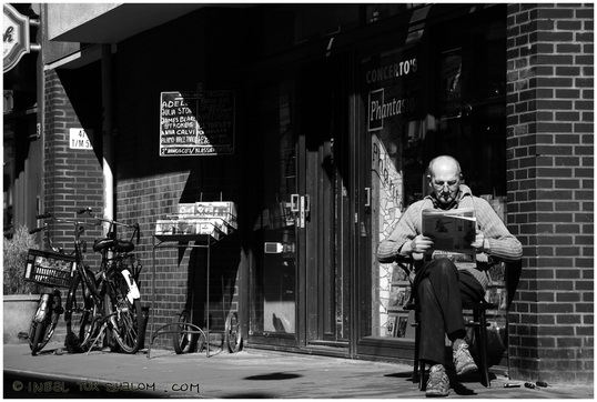 Contributor's Photo Gallery - Spring Photo Challenge - picture of a shop owner reading a book outside his establishment in Amsterdam.  Free Photo Lessons at www.FreePhotoCourse.com.© 2011, all rights reserved.