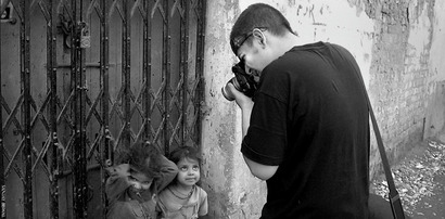 Photograph of Soham Gupta taking pictures of children in Calcutta, India.  Part of the Photographer Profile series from www.FreePhotoCourse.com.  all rights reserved