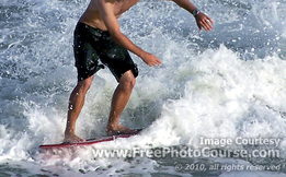 Picture of a surfer on a surfboard, riding a wave. Enjoy more free pictures from http://www.FreePhotoCourse.com.