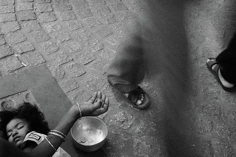 Picture of a child sleeping on the street in Calcutta, India, while the parent is begging for hand-outs.  Motion blur as people walk past this tearful scene.  Part of the Photographer Profiles series at FreePhotoCourse.com. © 2010, Soham Gupta, all rights reserved.