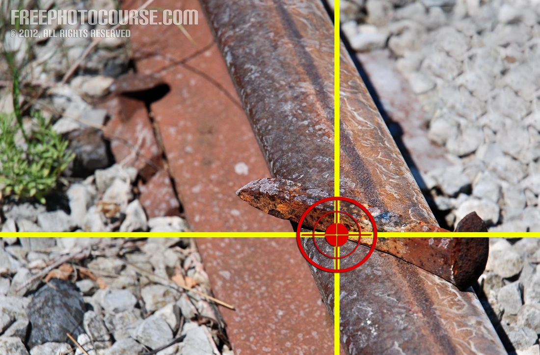 Picture of a rusty old iron spike on an abandoned railway track.  Rule of Thirds.  Part of a photo composition tutorial by FreePhotoCourse.com; © 2012, all rights reserved.